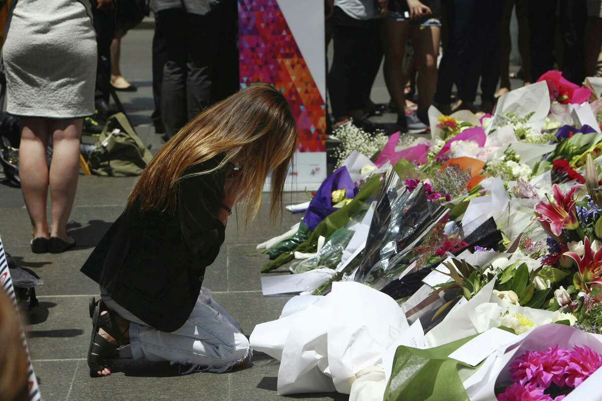 A woman kneels down as she lays flowers in a makeshift memorial near the site where a gunman held hostages for 16 hours at a popular Sydney cafe, Australia, Tuesday, Dec. 16, 2014. The siege ended early Tuesday with a barrage of gunfire that left two hostages and the Iranian-born gunman dead, and a nation that has long prided itself on its peace rocked to its core. (AP Photo/Steve Christo)