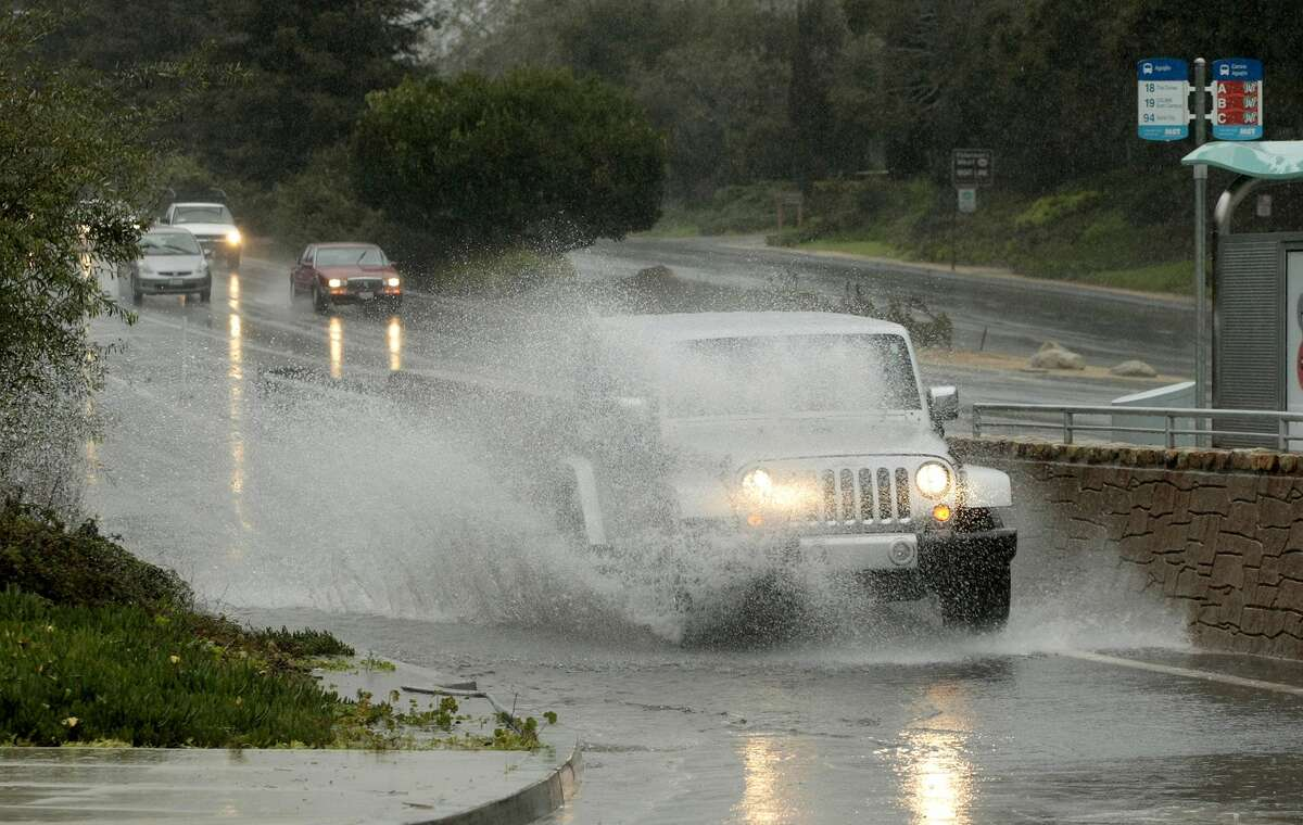 Heavy rain caused roadways to flood Monday, Dec. 15, 2014, in Monterey, Calif. A new storm dumped more rain on already waterlogged parts of Northern California, causing minor road flooding, scattered power outages and airport delays. The rain was coming down hard in the San Francisco Bay Area, making for a treacherous commute. A landslide closed both directions of a highway in Fremont. (AP Photo/Monterey Herald, Vern Fisher)