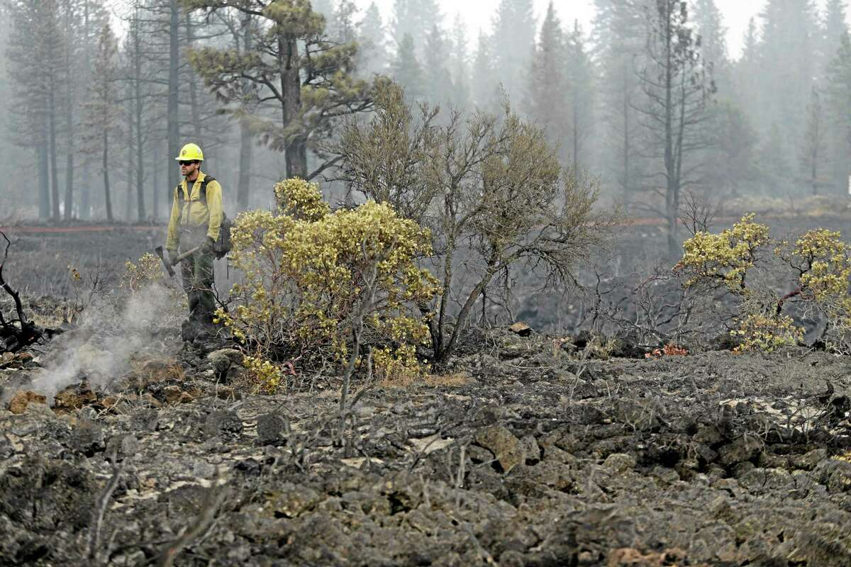 Remington Jones, of the Point Reyes National Seashore, Calif., Engine 1130, looks for hot spots left behind by the Eiler Fire on Aug. 5, near Burney, California, in this file photo.