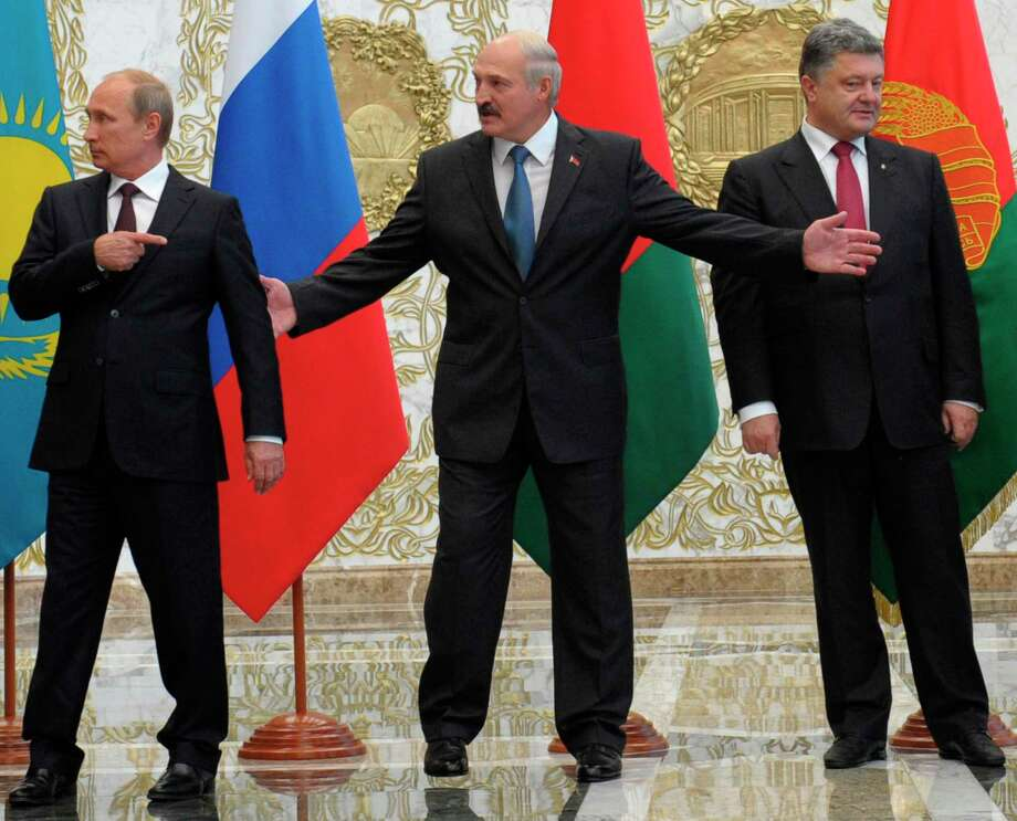 From left, Russian President Vladimir Putin,  Belarusian President Alexander Lukashenko and  Ukrainian President Petro Poroshenko stand before posing for a photo prior to talks in Minsk, Belarus, Tuesday, Aug. 26, 2014. The presidents of Russia and Ukraine sat down for talks Tuesday, meeting face-to-face for the first time since June on the fighting that has engulfed Ukraine's separatist east. (AP Photo/RIA-Novosti, Alexei Druzhinin, Presidential Press Service) Photo: AP / RIA Novosti Kremlin