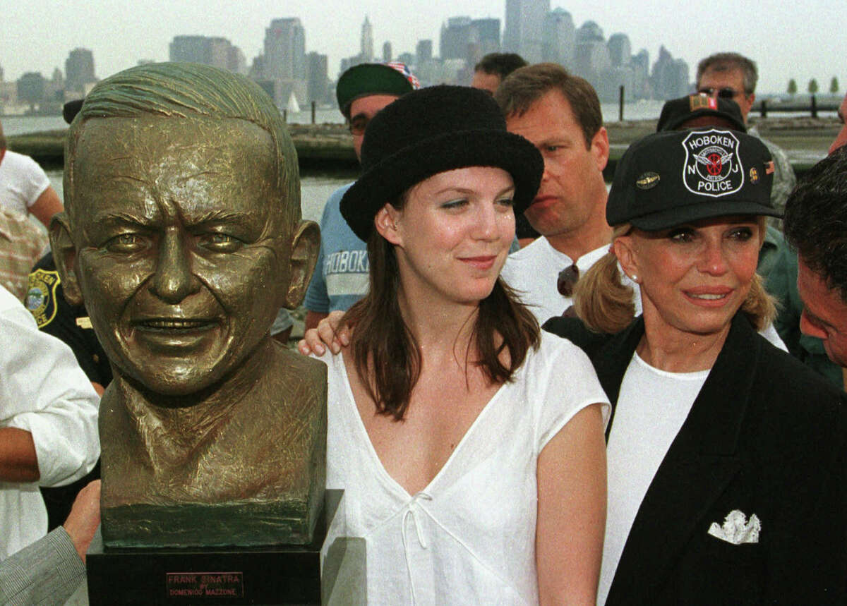 In this July 14, 1998, file photo, Nancy Sinatra, right, daughter of Frank Sinatra, and her daughter, A.J. Lambert stand next to a bust of Sinatra at the dedication of Frank Sinatra Memorial Park in Hoboken, N.J. Frank Sinatra, who died in 1998, at 82, would have celebrated his 100th birthday on Dec. 12, 2015.