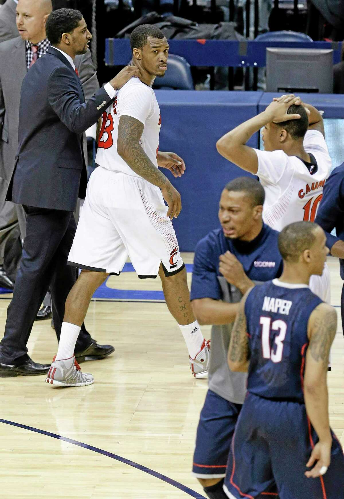 Cincinnati guard Sean Kilpatrick, top left, leaves the court as UConn guard Shabazz Napier celebrates with teammates after the Huskies' 58-56 win on Friday night in the semifinals of the American Athletic Conference tournament in Memphis, Tenn. Kilpatrick missed a layup in the final seconds.
