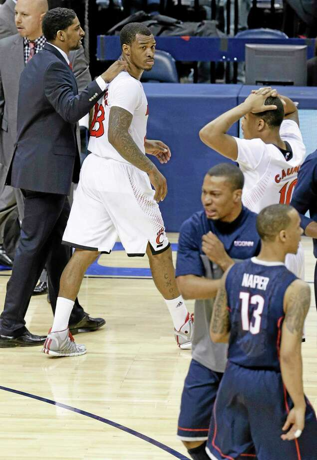 Cincinnati guard Sean Kilpatrick, top left, leaves the court as UConn guard Shabazz Napier celebrates with teammates after the Huskies' 58-56 win on Friday night in the semifinals of the American Athletic Conference tournament in Memphis, Tenn. Kilpatrick missed a layup in the final seconds. Photo: Mark Humphrey — The Associated Press  / AP