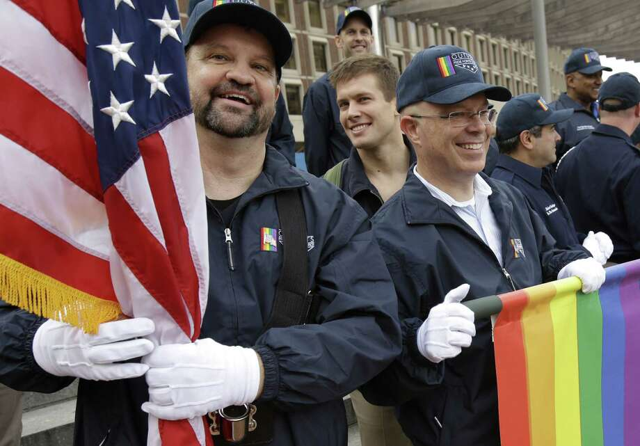 FILE - In this Nov. 11, 2014 file photo, retired U.S. Air Force Master Sgt. Eric Bullen, of Westborough, Mass., left, holds an American flag as U.S. Army veteran Ian Ryan, of Dennis, Mass., front right, rolls up an OutVets banner after marching with a group representing LGBT military veterans in a Veterans Day parade in Boston. The organizers of Boston's annual St. Patrick's Day parade voted to allow the group of gay veterans to march in the 2015 parade, a turnaround for the organization that has long resisted the inclusion of gays. (AP Photo/Steven Senne, File) Photo: AP / AP