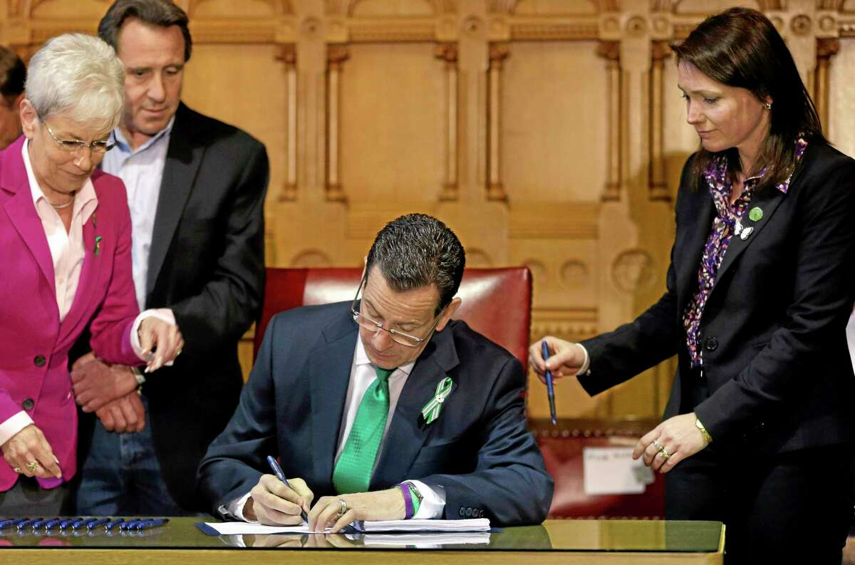 In this April 4, 2013, file photo, Connecticut Gov. Dannel P. Malloy, center, signs legislation at the Capitol in Hartford that includes new restrictions on weapons and large capacity ammunition magazines. Surrounding him are Lt. Gov. Nancy Wyman, left, Neil Heslin, second left, father of shooting victim Jesse Lewis, and Nicole Hockley, right, mother of shooting victim Dylan.