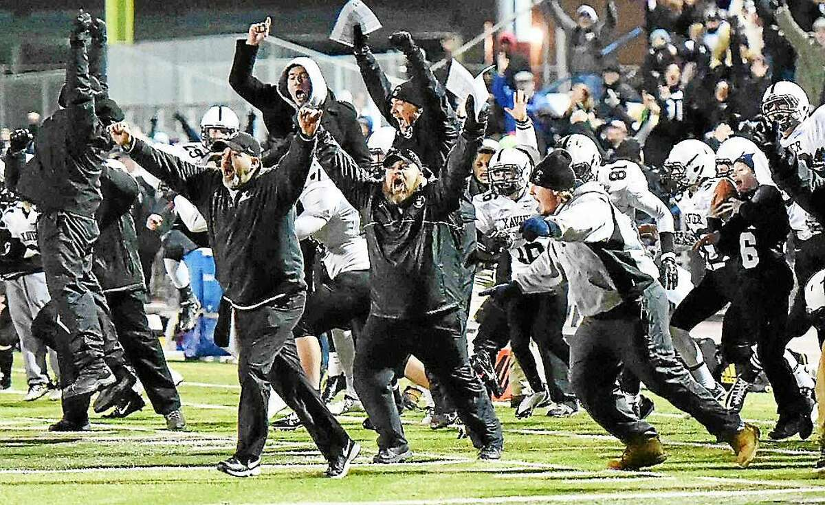 Xavier's sideline reacts to winning the Class LL-Small title over Shelton 28-27 in overtime last year