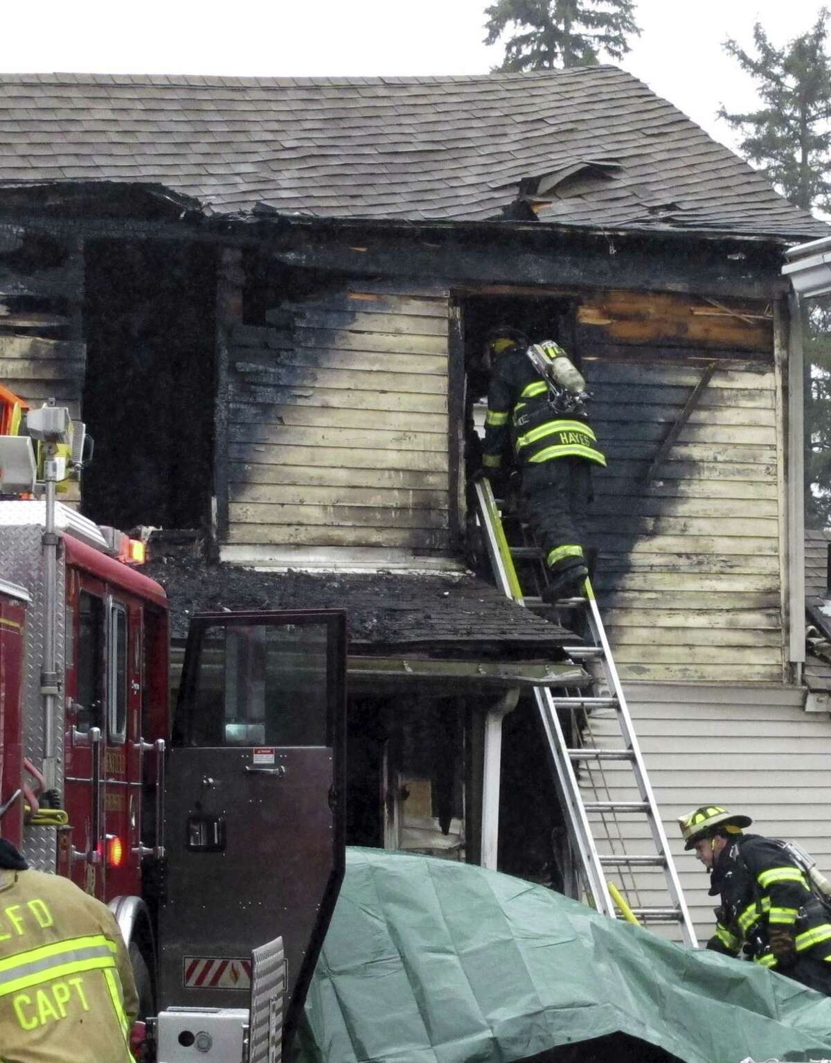 Firefighters work the scene of a house blaze Wednesday, Dec. 10, 2014, in Enfield, Conn., about 20 miles north of Hartford. Officials said four people were unaccounted for.