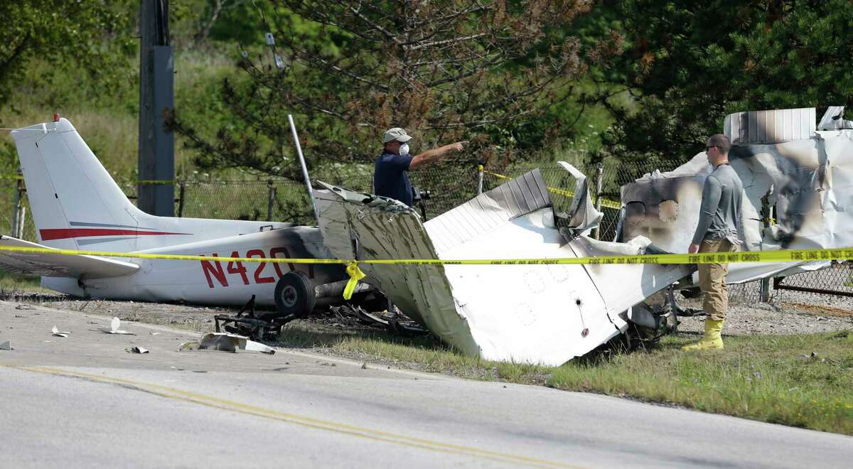 Investigators look over the wreckage of a plane crash as it rests on the side of a road Tuesday, Aug. 26, 2014, in Richmond Heights, Ohio. The Cessna 172R crashed and burst into flames just after takeoff from a regional airport outside of Cleveland on Monday, killing all four people on board, according to the Ohio State Highway Patrol. School officials say the three passengers killed in he crash were members of the varsity wrestling team for Case Western Reserve University in Cleveland. (AP Photo/Tony Dejak)