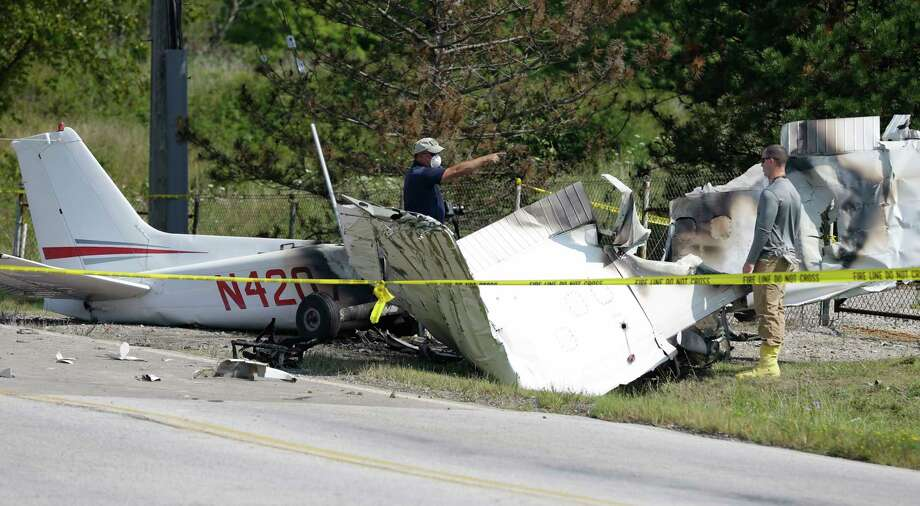 Investigators look over the wreckage of a plane crash as it rests on the side of a road Tuesday, Aug. 26, 2014, in Richmond Heights, Ohio. The Cessna 172R crashed and burst into flames just after takeoff from a regional airport outside of Cleveland on Monday, killing all four people on board, according to the Ohio State Highway Patrol.   School officials say the three passengers killed in he crash were members of the varsity wrestling team for Case Western Reserve University in Cleveland. (AP Photo/Tony Dejak) Photo: AP / AP
