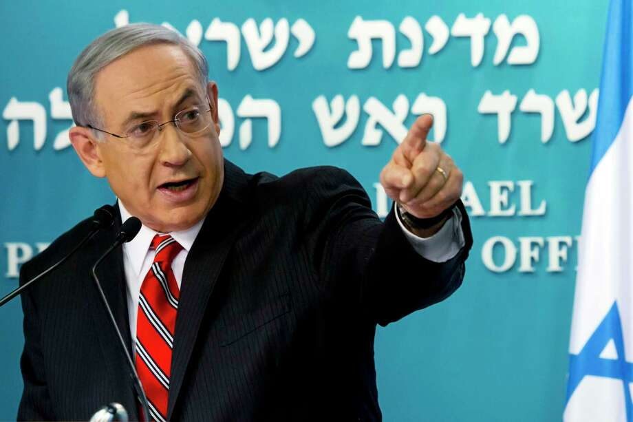 """FILE - In this Wednesday, Aug. 6, 2014, file photo, Israeli Prime Minister Benjamin Netanyahu points at a video screen showing Hamas militants firing rockets into Israel from areas near schools and Hamas deploying civilians as human shields, as he gives a news conference in Jerusalem. A day after the Islamic State group, also known as ISIS, posted the video of American journalist James Foley's killing, Netanyahu debuted his latest catchphrase: """"Hamas is ISIS. ISIS is Hamas."""" Photo: (AP Photo/Jim Hollander, Pool, File) / Pool EPA"""