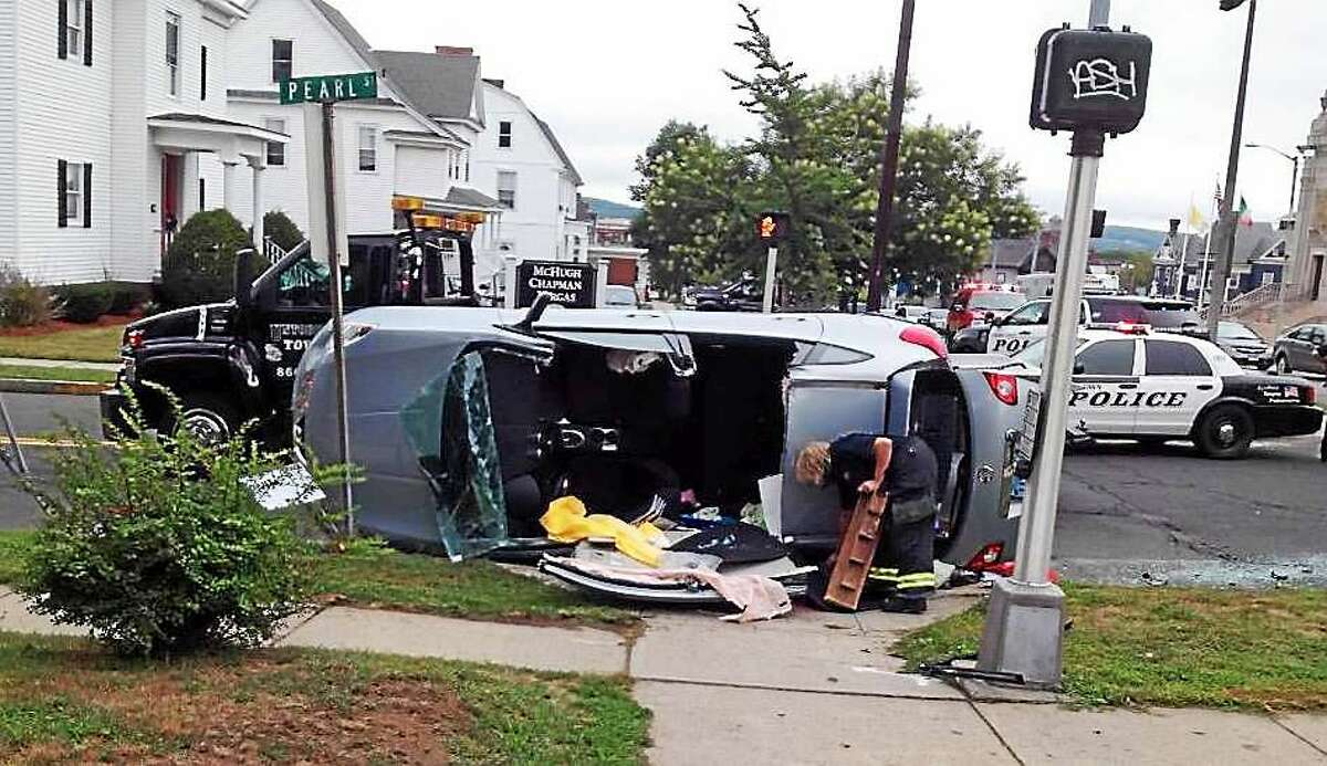 BRIAN ZAHN — THE MIDDLETOWN PRESS Rescue crews used the Jaws of Life to free a woman from her car after it crashed and rolled over Friday morning at Pearl and Washington streets in Middletown.
