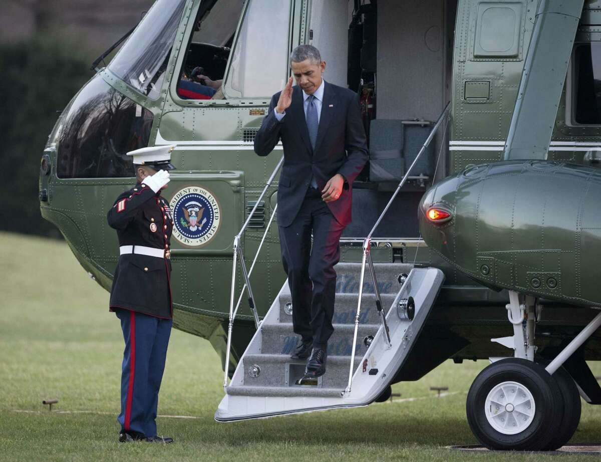 President Barack Obama returns a salute as he steps off Marine One helicopter upon his return on the South Lawn of the White House in Washington, Monday, Dec. 15, 2014.