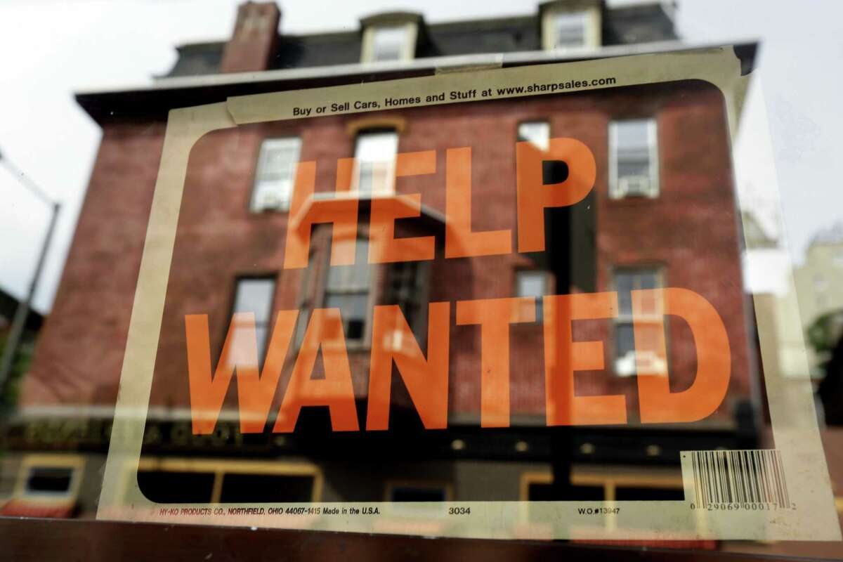In this file photo, a Philadelphia business displays a help wanted sign in its storefront.