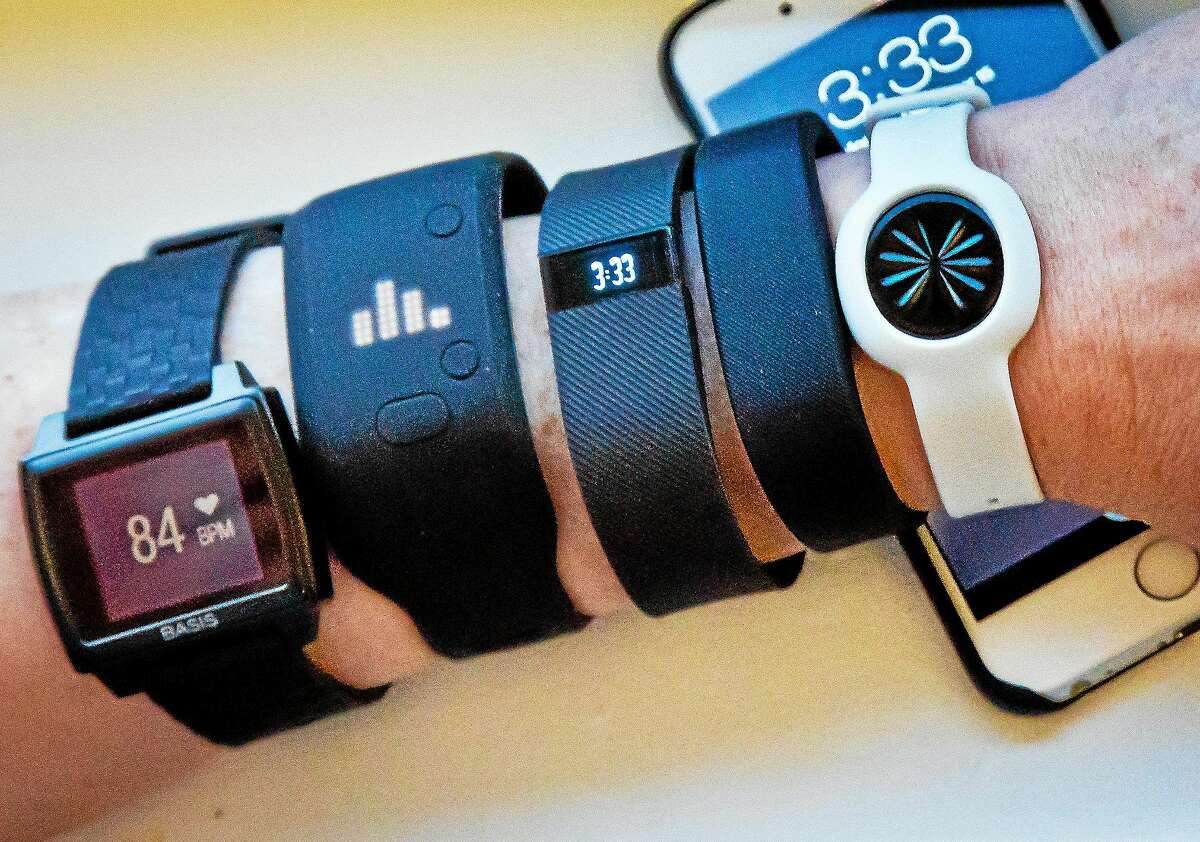 Fitness trackers, from left: Basis Peak, Adidas Fit Smart, Fitbit Charge, Sony SmartBand, and Jawbone Move, are posed for a photo next to an iPhone.
