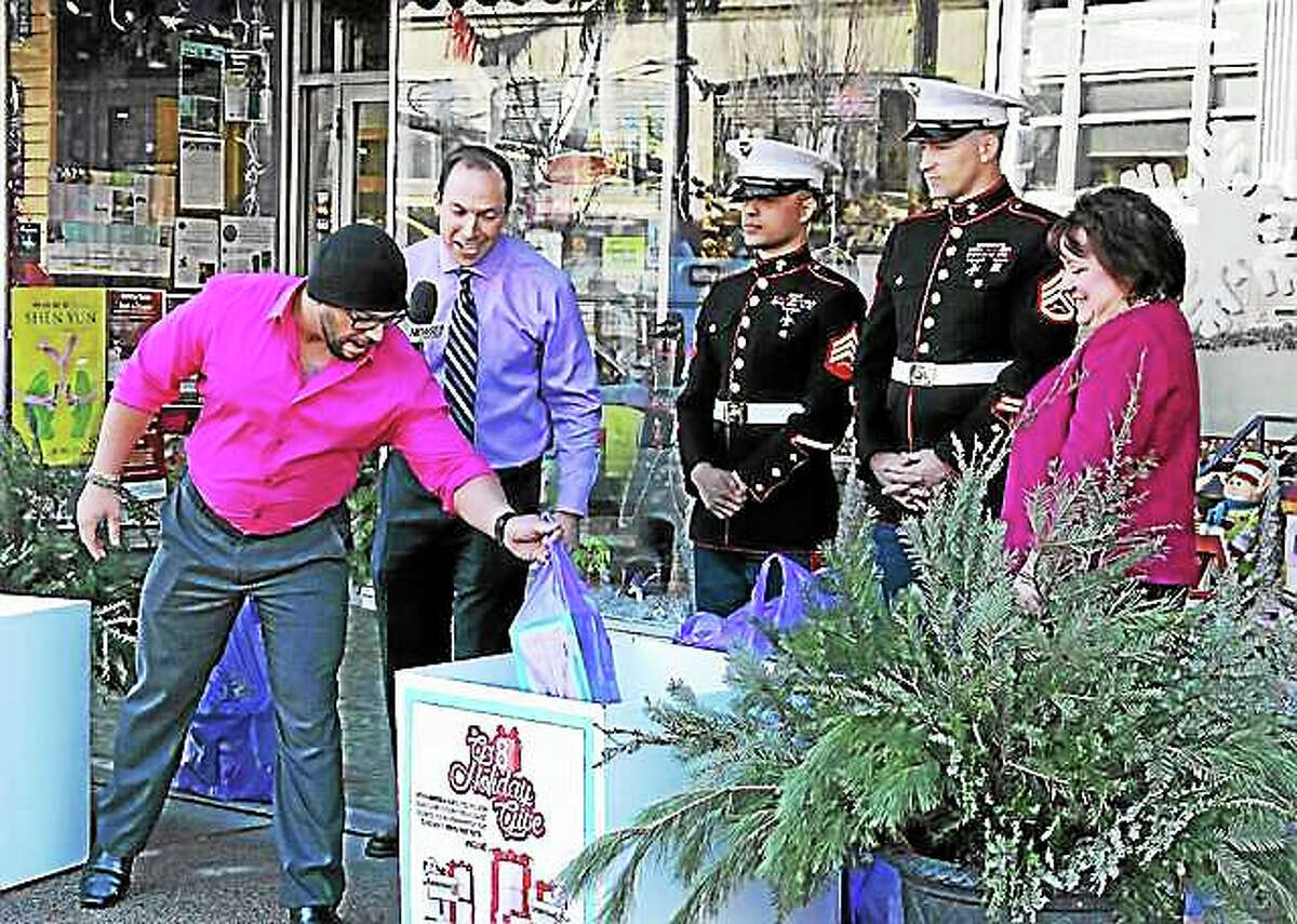 Channel 8 meteorologist Gil Simmons interviews a military veteran before he donates a gift Thursday to Toys for Tot's. The toy drive was organized with help from the U.S. Marines in front of Amato's Toy & Hobby on Main Street. Amato's Diane Jervis stands at far right.
