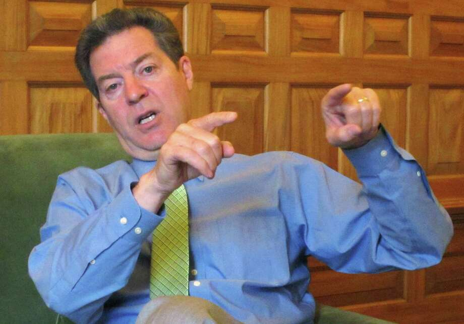 In this April 13, 2015 photo, Kansas Republican Gov. Sam Brownback makes a point during an interview in his office in the Statehouse in Topeka, Kan. Brownback is preparing to sign welfare legislation restricting how poor families can spend cash assistance from the state. The Republican governor scheduled a Thursday, April 16, 2015, morning signing ceremony at the Statehouse. (AP Photo/John Hanna) Photo: AP / AP
