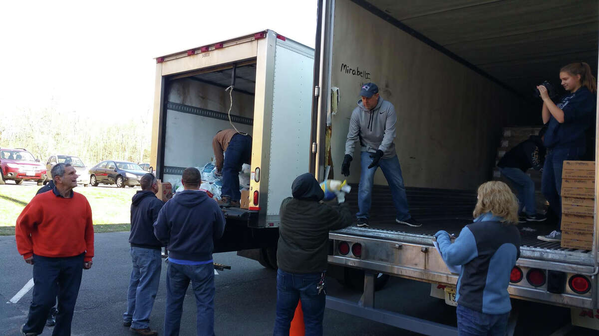 Middletown Community Thanksgiving Project volunteers load turkeys into trucks donated by PJ Mirabelli Enterprises and Jukonski Truck. Vehicles were also contributed by Stor-U-Self Portland and Penske for the project, and buses from DATTCO and Middletown Area Transit.