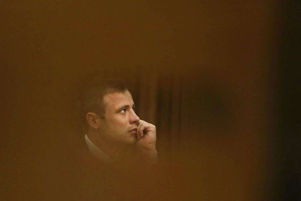 In this Oct. 16, 2014 file photo, Oscar Pistorius sits in the high court for the fourth day of sentencing in Pretoria, South Africa.