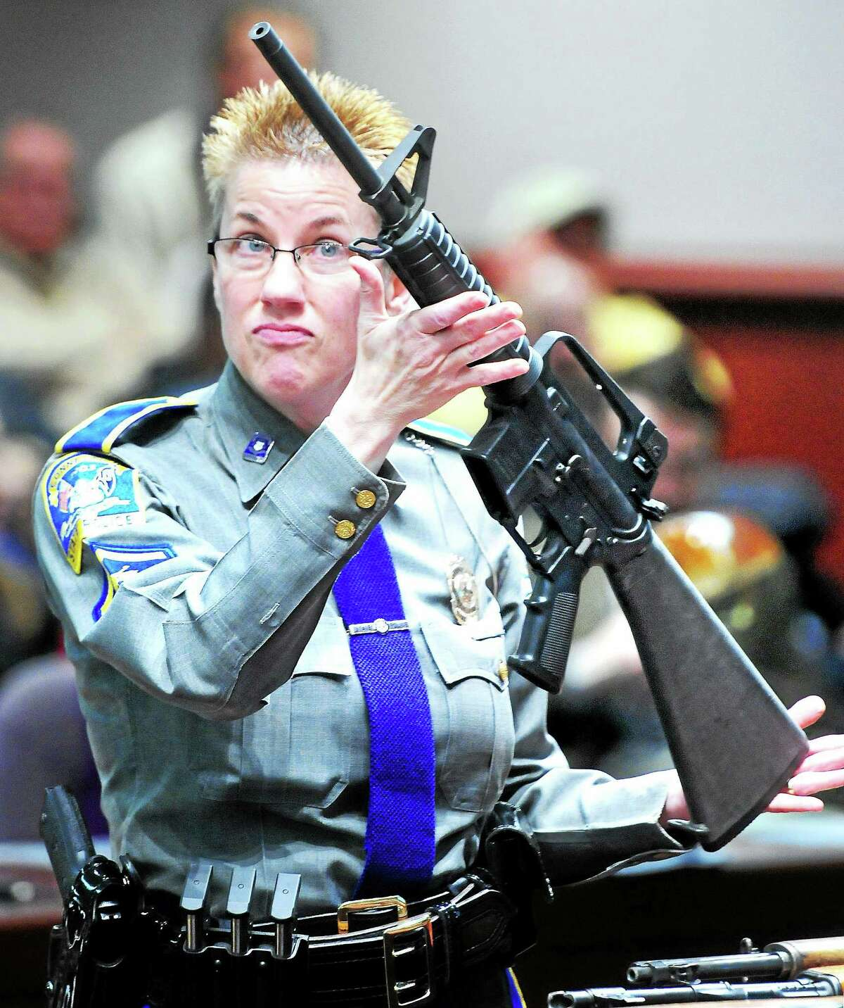Connecticut State Police Detective Barbara Mattson holds up a Bushmaster rifle during a legislative hearing about gun control at the Legislative Office Building in Hartford on Jan. 28, 2013.