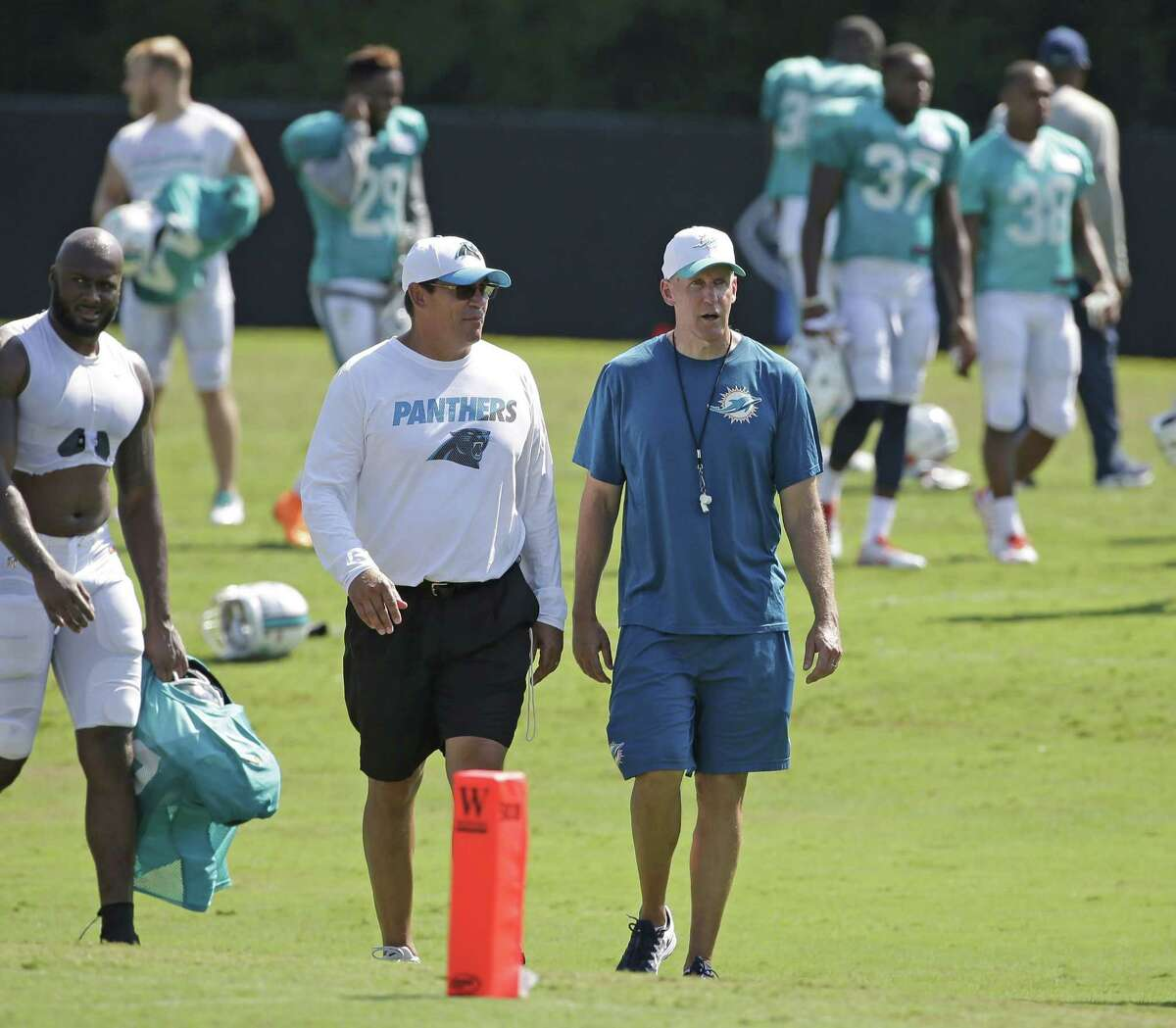 Carolina Panthers head coach Ron Rivera, left, and Miami Dolphins head coach Joe Philbin, right, talk as they walk off the field Wednesday after a joint practice at the Panthers' training camp in Spartanburg, S.C.
