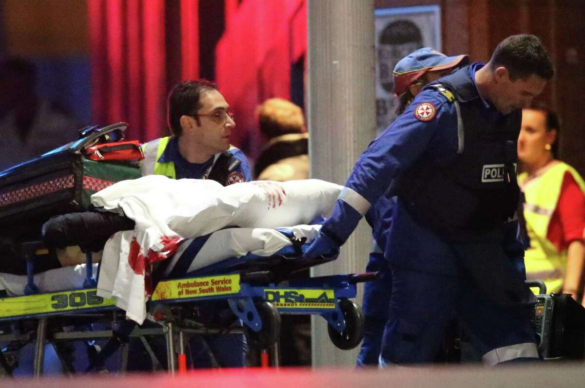 A blood soaked stretcher is wheeled to an ambulance after shots were fired Tuesday during a cafe under seige at Martin Place in the central business district of Sydney, Australia. A flurry of loud bangs erupted as a swarm of heavily armed police stormed inside a downtown Sydney chocolate cafe where a gunman had been holding an unknown number of people hostage for more than 16 hours.