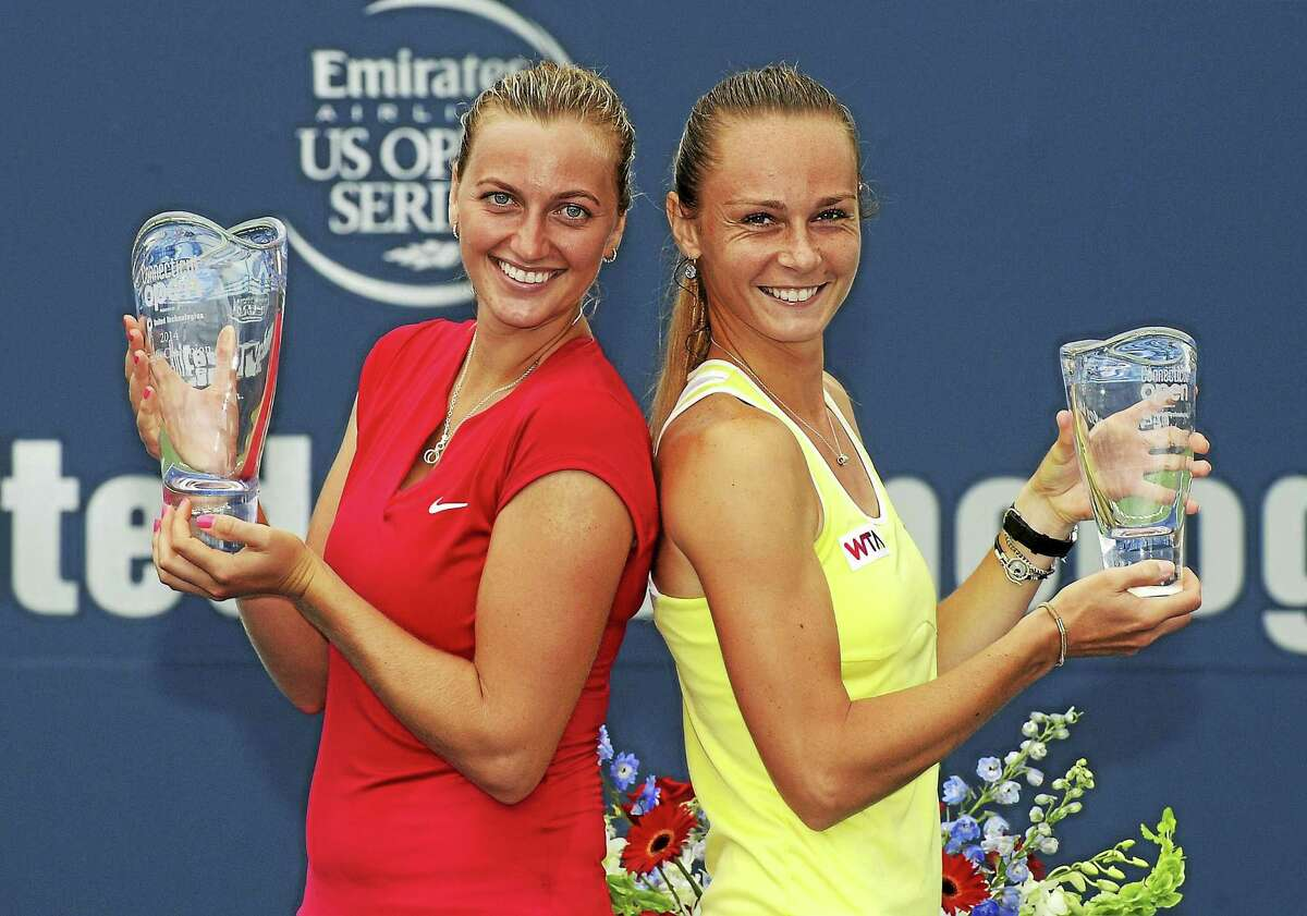 Petra Kvitova, of the Czech Republic, left, and Magdalena Rybarikova, of Slovakia, celebrate after Kvitova's 6-4, 6-2 victory in the final match of the Connecticut Open tennis tournament in New Haven, Conn., on Saturday, Aug. 23, 2014. (AP Photo/Fred Beckham)