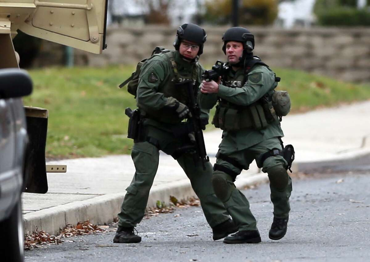 Police move near the scene of a shooting, Monday, Dec. 15, 2014, in Souderton, Pa. Police are surrounding a home in Souderton, outside Philadelphia, where a suspect is believed to have barricaded himself after shootings at multiple homes. Police tell WPVI-TV the man is suspected of killing a five people Monday morning at three different homes.