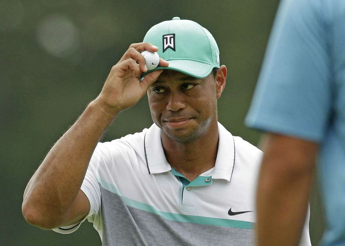 Tiger Woods tips his hat to the crowd after finishing his round Thursday at the Wyndham Championship in Greensboro, N.C.