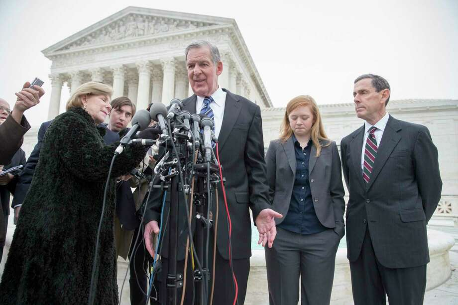 Abigail Fisher, second from right, who challenged the use of race in college admissions, listens as her lawyer Bert Rein, center, speaks with reporters outside the Supreme Court in Washington Wednesday, following oral arguments in the Supreme Court in a case that could cut back on or even eliminate affirmative action in higher education. At far right is attorney Edward Blum. Photo: J. Scott Applewhite — The Associated Press  / AP