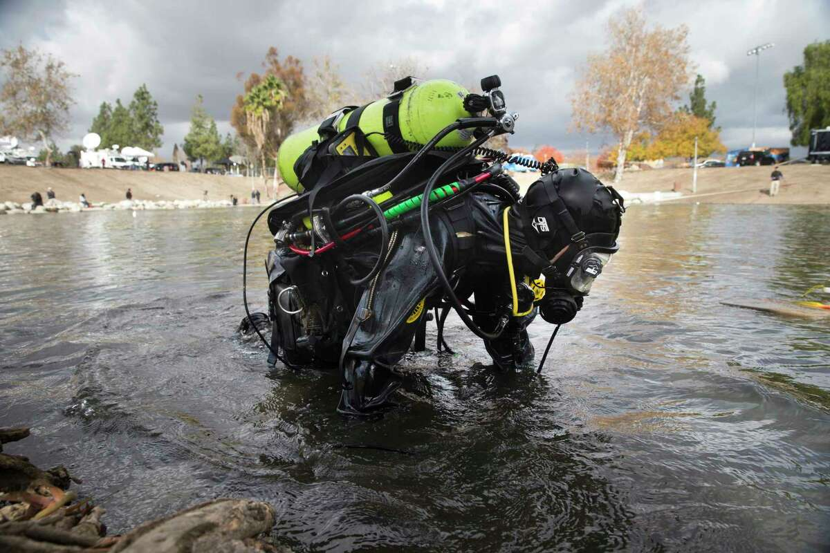 A member of the FBI dive team searches Seccombe Lake Friday in San Bernardino, Calif., for evidence in connection with last week's fatal shooting at Inland Regional Center.