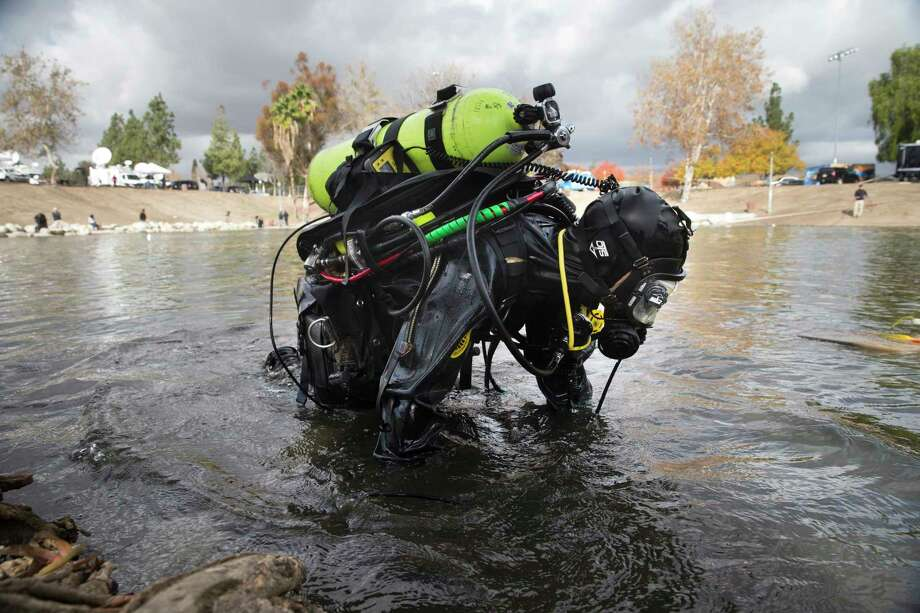 A member of the FBI dive team searches Seccombe Lake Friday in San Bernardino, Calif., for evidence in connection with last week's fatal shooting at Inland Regional Center. Photo: Jae C. Hong — The Associated Press  / AP