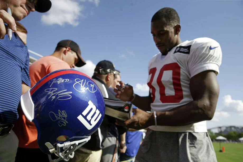 New York Giants wide receiver Victor Cruz, right, signs autographs after the Giants' joint NFL football training camp with the Cincinnati Bengals, Tuesday, Aug. 11, 2015, in Cincinnati. (AP Photo/John Minchillo) Photo: AP / AP