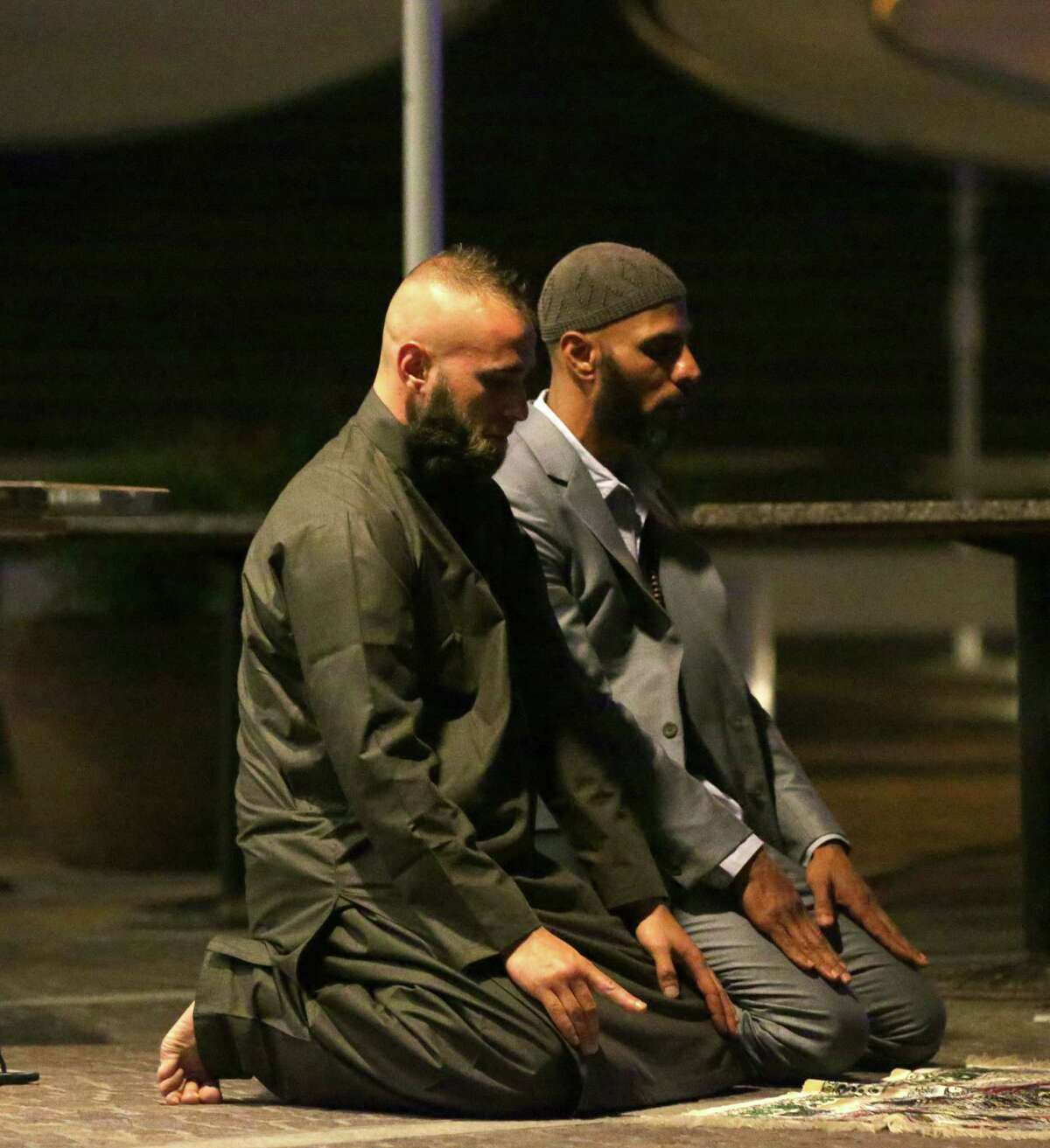 Sam Tiger right, and Abdulrahman El-Lawn perform prayers after a cafe siege in the central business district of Sydney , Australia, Tuesday, Dec. 16, 2014. This was their first prayer of the morning and prayed for peace and to bring comfort upon those affected especially the hostages and their families. They both made a second prayer directed towards Muslims to make the aftermath a peaceful one. (AP Photo/Glenn Nicholls)
