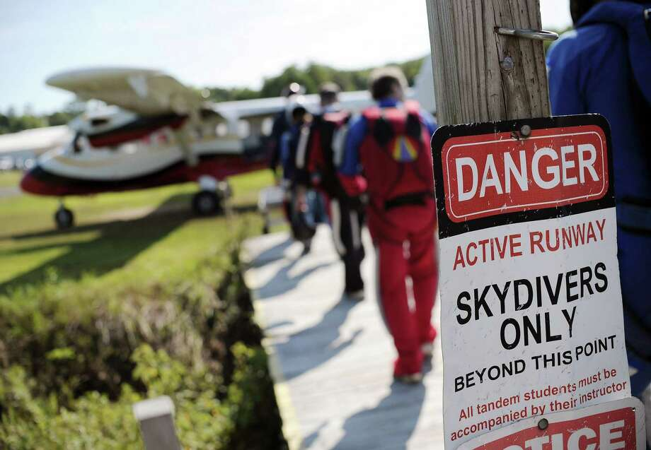In this Friday, Aug. 7, 2015 photo, parachuters walk toward a jump plane at Ellington Airport in Ellington, Conn. Alex Kelly worked for six years for Connecticut Parachutists Inc., headquartered at the airport, and rose to president of the organization before being asked to resign in 2014. Officials of the skydiving club said Kelly is trying to buy the airport, which would give him control over the club's lease. Photo: AP Photo/Jessica Hill  / FR125654 AP