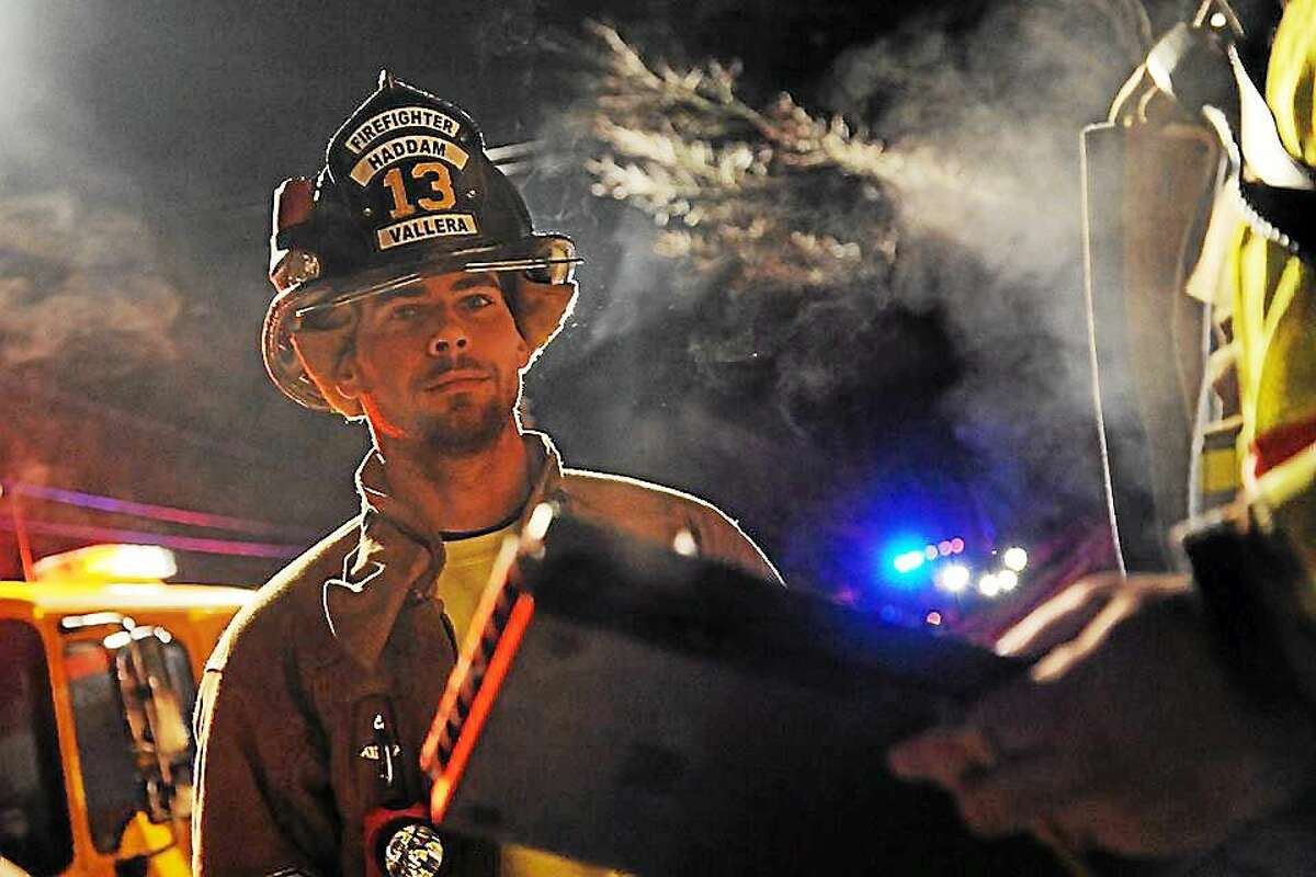Haddam Volunteer Firefighter Kyle Vallera helps remediate the smoke from an overheated sump pump at a basement on Dublin Hill Road Dec. 11.