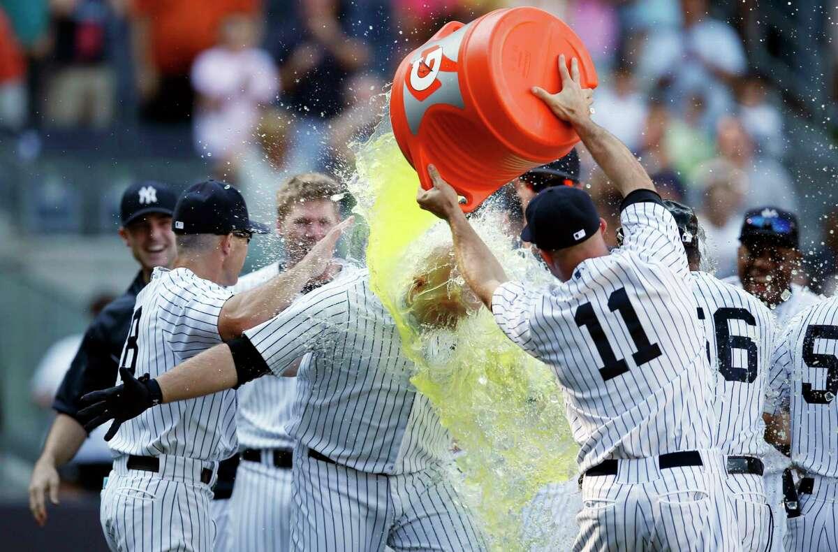 The Yankees' Brett Gardner (11) douses teammate Brian McCann after McCann hit a three-run home run in the 10th inning Sunday.