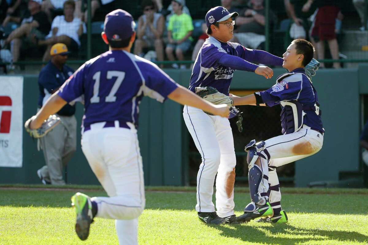 South Korea's Hae Chan Choi, center, celebrates with catcher Sang Hoon Han, right, after getting the final out of a 8-4 win in the Little League World Series championship game against Chicago on Sunday.