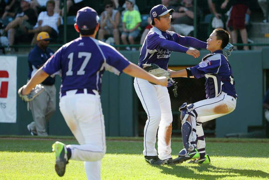 South Korea's Hae Chan Choi, center, celebrates with catcher Sang Hoon Han, right, after getting the final out of a 8-4 win in the Little League World Series championship game against Chicago on Sunday. Photo: Gene J. Puskar — The Associated Press  / AP
