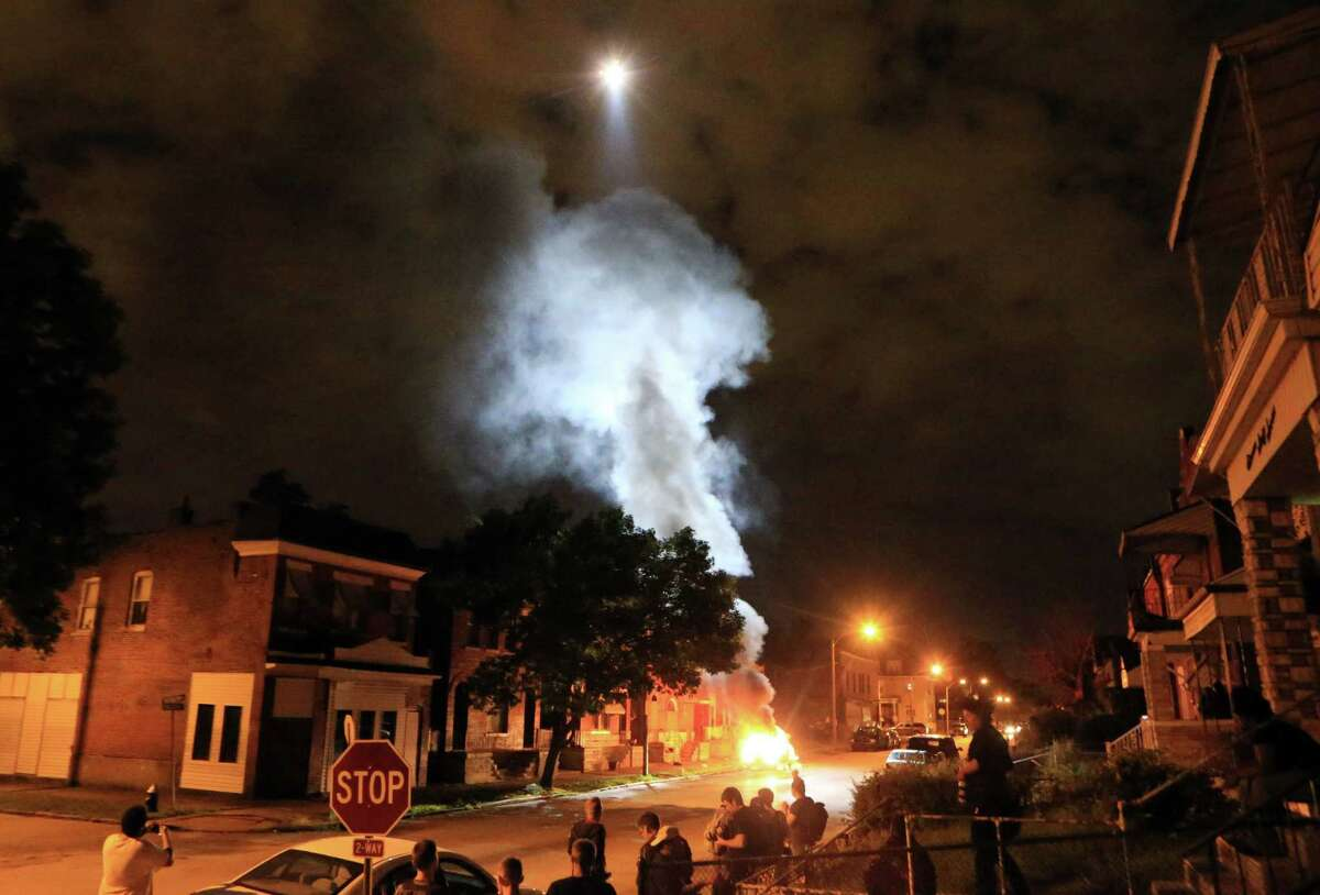 A police helicopter illuminates a burning car Wednesday, Aug. 19, 2015, after it was set ablaze following a fatal officer-involved shooting, in St. Louis. A black 18-year-old fleeing from officers serving a search warrant at a home in a crime-troubled section of St. Louis was fatally shot Wednesday by police after he pointed a gun at them, the city's police chief said.