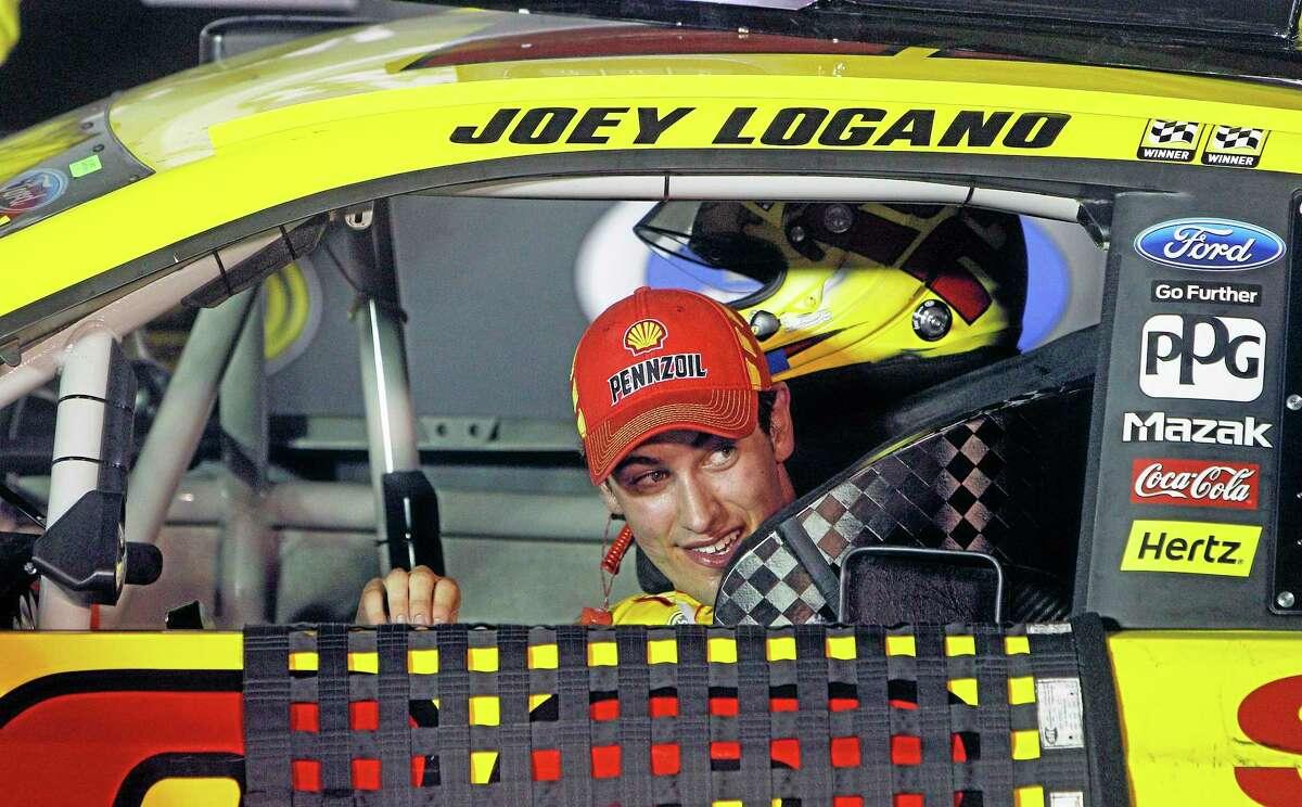 Driver Joey Logano peeks out his window as he pulls into victory lane after winning Saturday night in Bristol, Tenn.