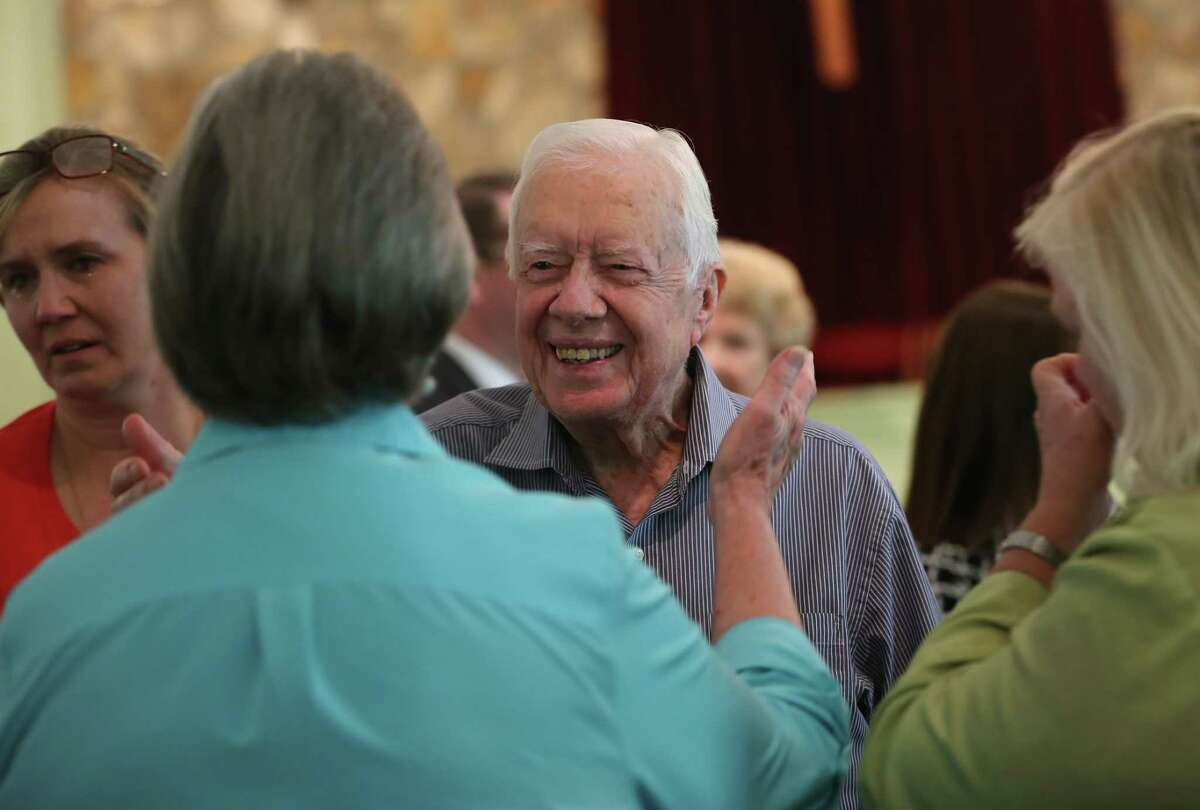 In this Sunday, Aug. 16, 2015 photo, former President Jimmy Carter reaches to embrace his brother Billy's widow, Sybil, while greeting family following service at Maranatha Baptist Church in Plains, Ga. Carter's nieces Mandy Flynn, left, and Jana Carter are also pictured.