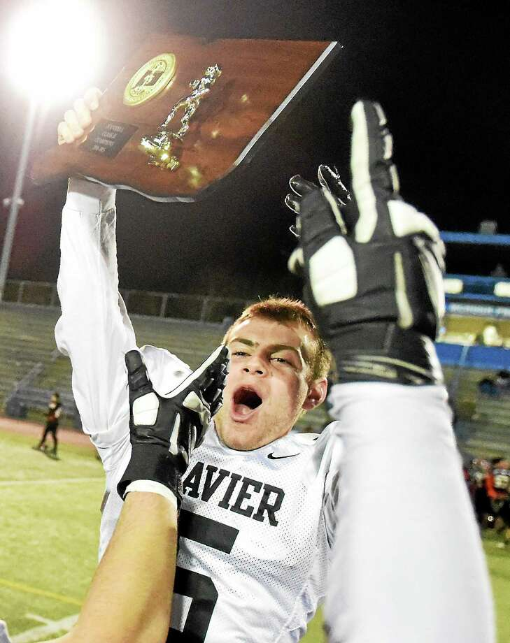 Michael Scherer, who, scored from five yards out in overtime holds the championship plaque as fourth-seeded Xavier came from behind to stun second-seeded and previously unbeaten SCC rival Shelton on Saturday. Photo: Peter Hvizdak — New Haven Register  / ©2014 Peter Hvizdak