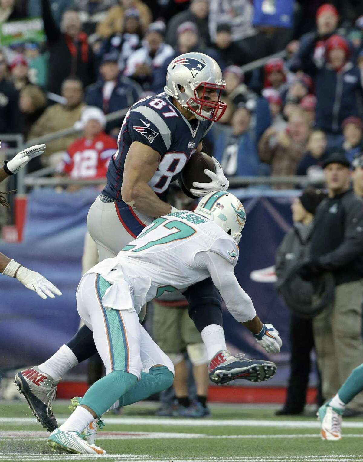 New England Patriots tight end Rob Gronkowski, top, advances the ball while under pressure from Miami Dolphins strong safety Jimmy Wilson, below, in the second half of an NFL football game Sunday, Dec. 14, 2014, in Foxborough, Mass. (AP Photo/Steven Senne)