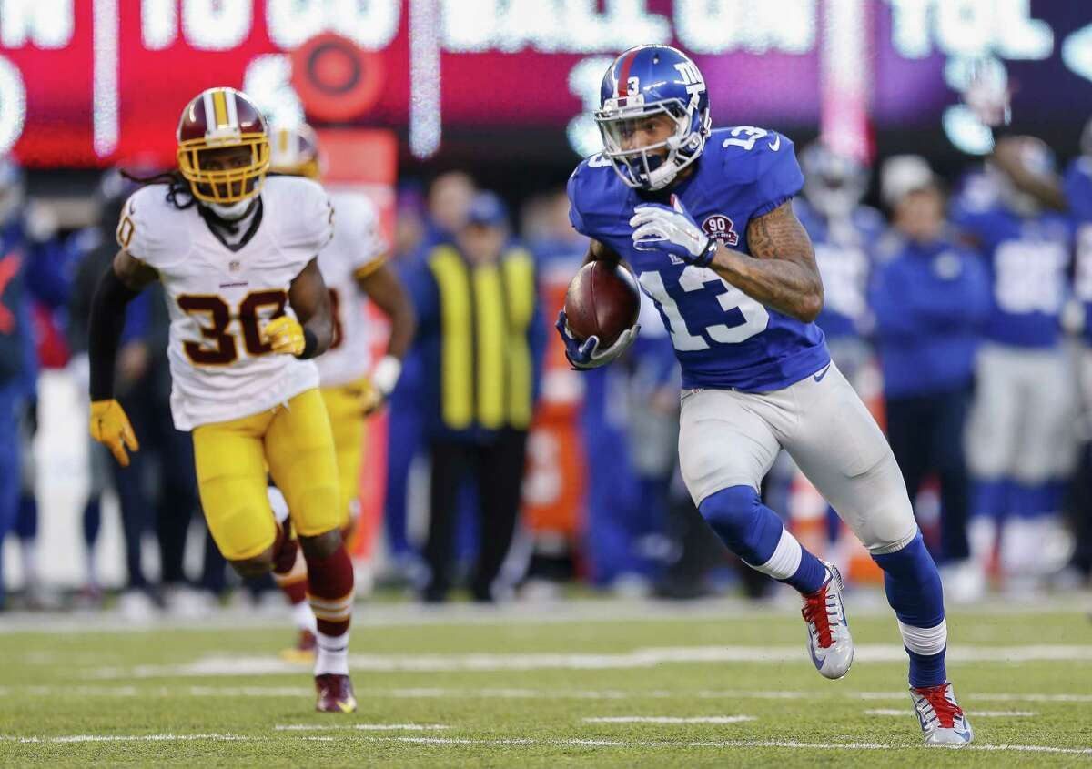 New York Giants wide receiver Odell Beckham (13) takes the ball for a touchdown as Washington Redskins free safety E.J. Biggers (30) pursues during the third quarter of an NFL football game, Sunday, Dec. 14, 2014, in East Rutherford, N.J. (AP Photo/Julio Cortez)