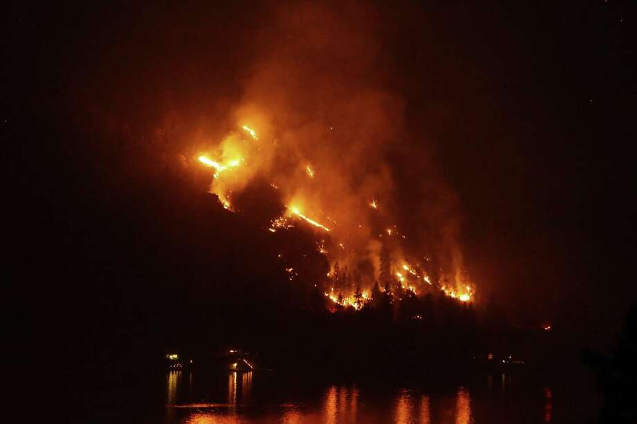 Timber burns in the First Creek fire near lakeside structures on the western shore of Lake Chelan late Monday, Aug. 17, 2015, near Chelan, Wash. Big wildfires threatened the Lake Chelan resort region of central Washington on Monday after driving away tourists, destroying a warehouse filled with nearly 2 million pounds of apples and forcing thousands of residents to flee. Photo: AP Photo/Ted S. Warren / AP