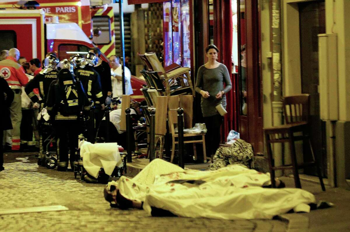 In this Nov.13, 2015, file photo, a woman watches victims lying outside Le Belle Equipe restaurant in Paris. All the attackers and accomplices so far identified were raised in Europe, native French speakers with roots in the marginalized immigrant communities of France and Belgium. Minor players — like the man who rented a room to the attacks' mastermind, Abdelhamid Abaaoud — have a degree or two of separation in an underworld of drugs, fraud and theft.