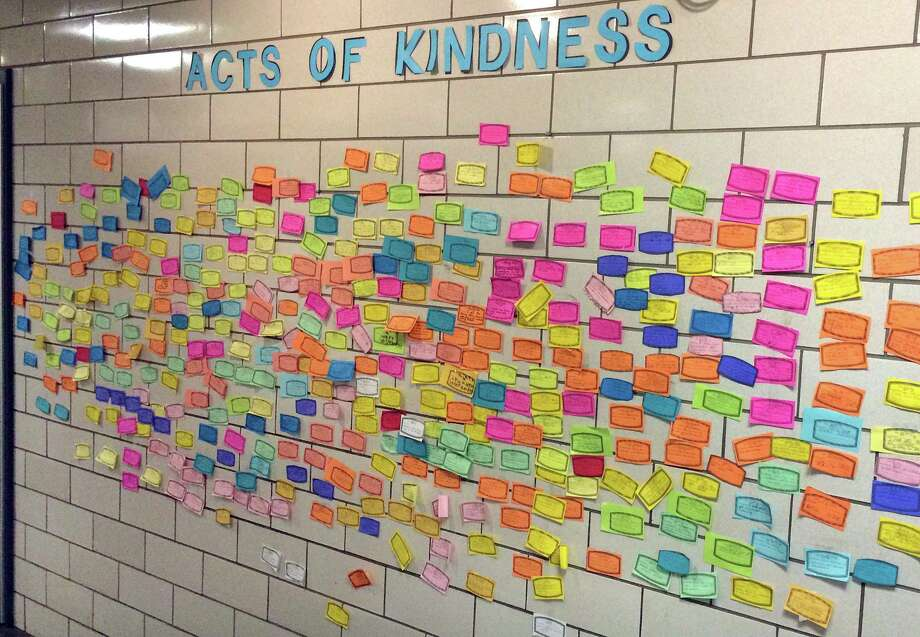 In this Dec. 1, 2015, photo, slips of paper listing acts of kindness adorn the wall of the Pleasant Valley Elementary School in South Windsor.  The school is one of many across the country asking children to perform 26 acts of kindness on the third anniversary of the shooting at the Sandy Hook Elementary school that took 26 lives. The children at Pleasant Valley, many of whom are too young to remember the shooting, are not being told about the origin of the program. Photo: AP Photo/Michael Melia   / AP