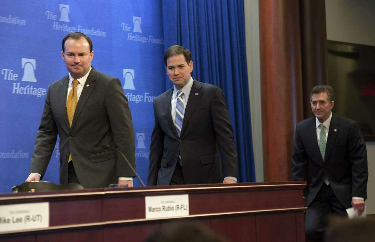 Republican presidential candidate, Sen. Marco Rubio, R-Fla., center, accompanied by Sen. Mike Lee, R-Utah, left, and Heritage Foundation President Jim DeMint, arrive to discuss their recently released tax reform plan April 15 at the Heritage Foundation in Washington.
