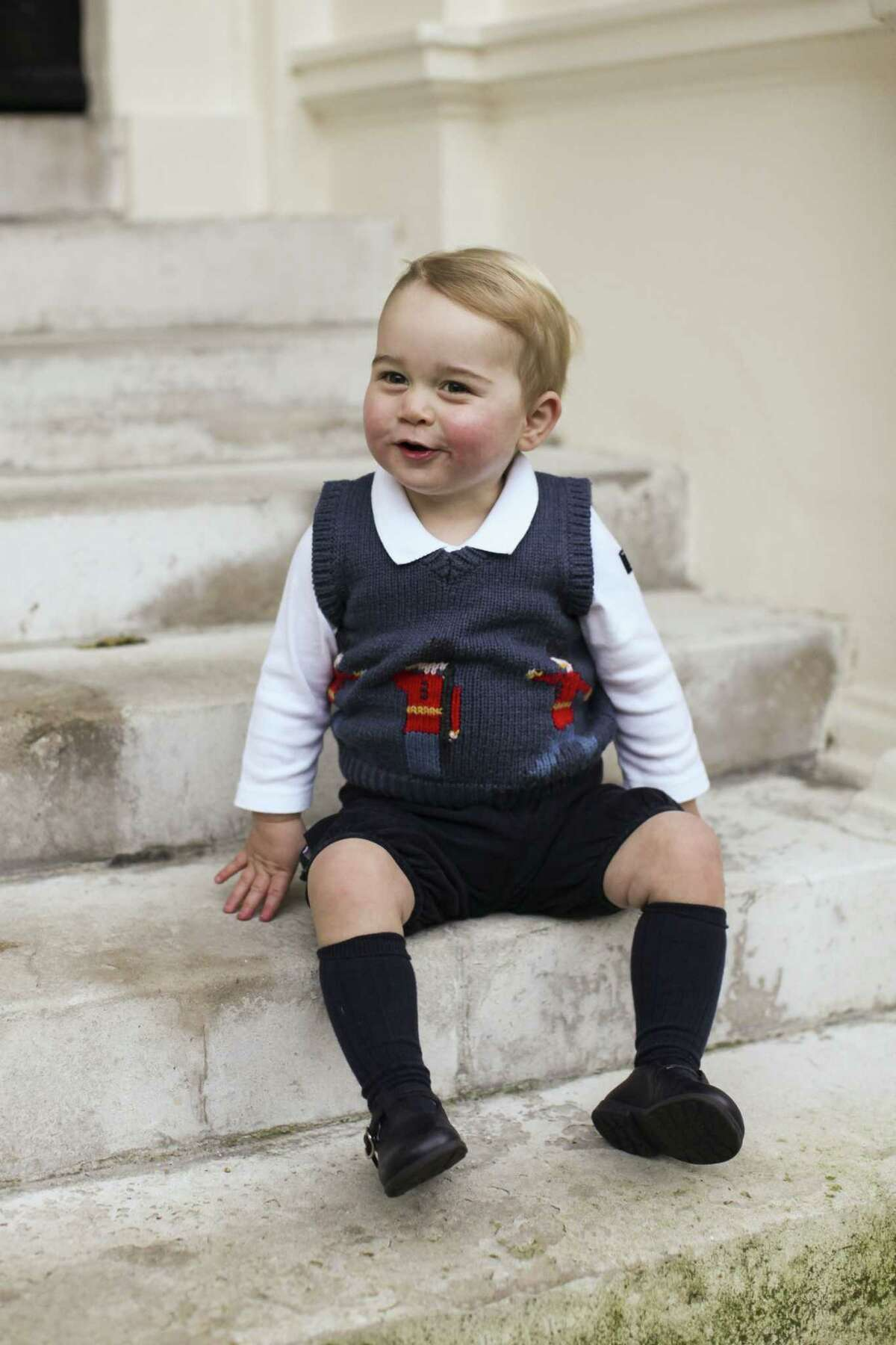In this photo provided by The Duke and Duchess of Cambridge and taken in late Nov. 2014, Britain's Prince George poses for a photograph in a courtyard at Kensington Palace, London. Great-grandchild to Britain's Queen Elizabeth II, Prince George was born July 22, 2013 and is third in line to the British throne.