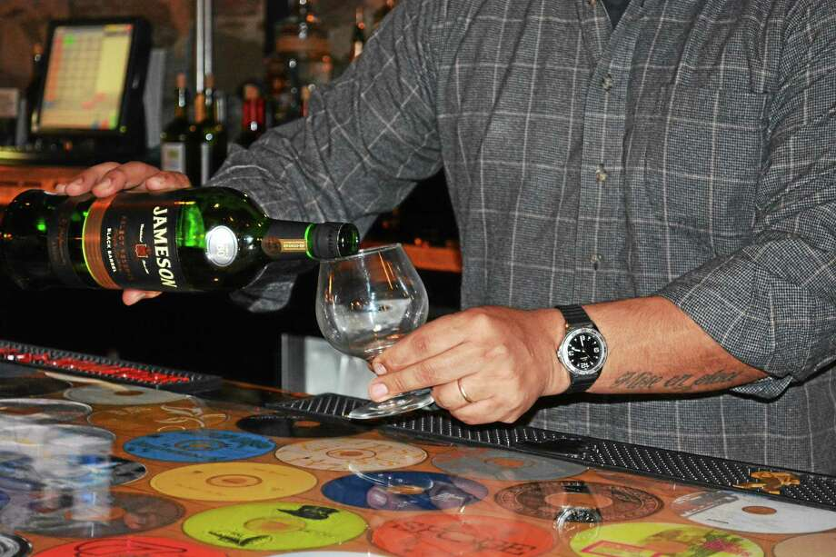 Jay Escudero, general manager of the Celtic Cavern at Main Street Market in Middletown, pours a drink behind the pub's bar. Following a misunderstanding last month, the gastropub is celebrating St. Patrick's Day this year in April. Photo: Brian Zahn — The Middletown Press